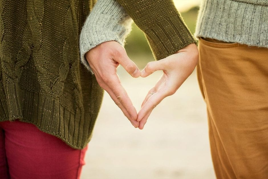 a couple making the heart symbol with their hands