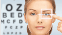woman pointing to her eye and an eye testing board behind her