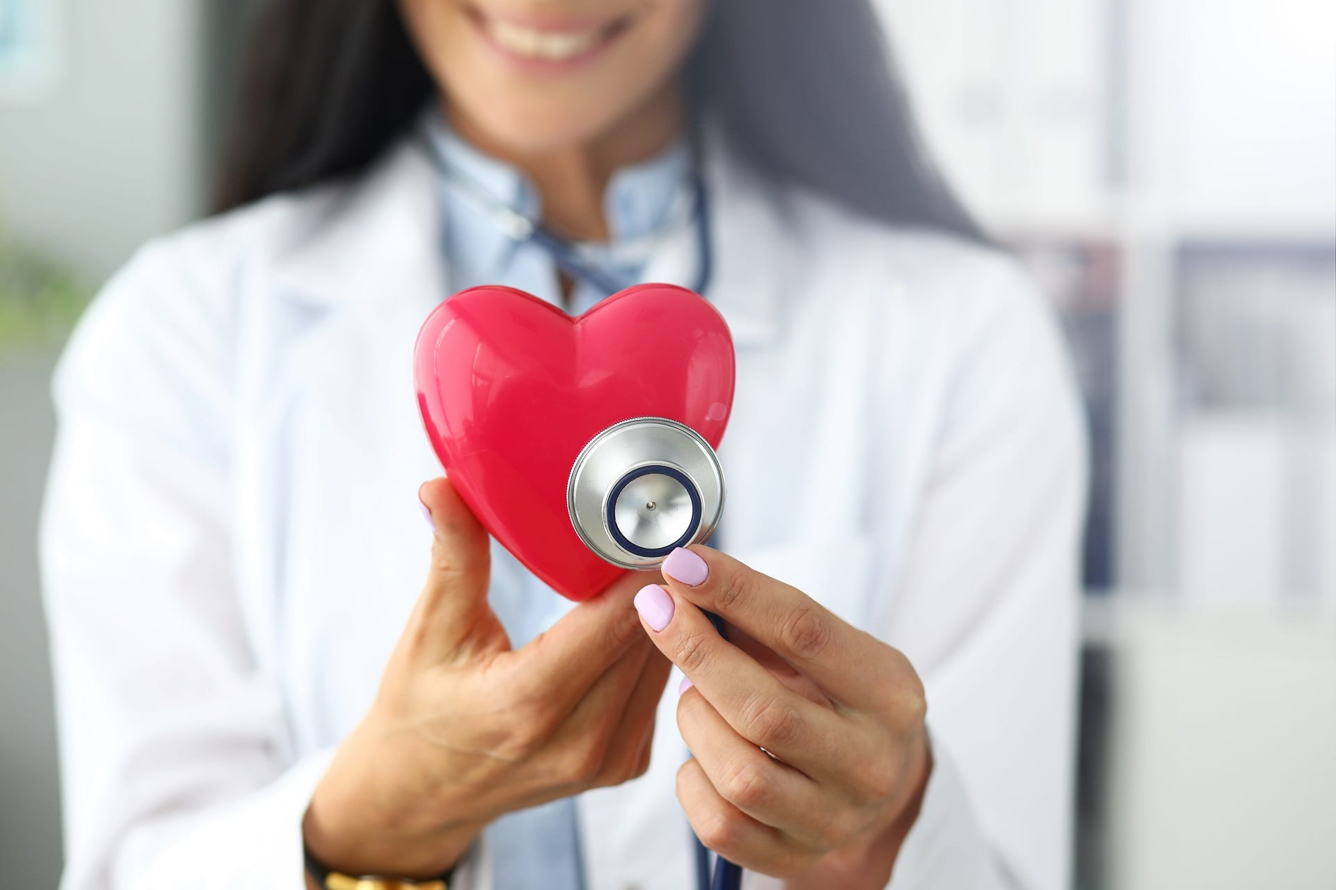 Hands of female GP holding stethoscope head near red toy heart